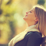 Young happy woman enjoying fresh air in autumn, intentionally to